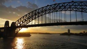 在悉尼港桥后的日落 免版税库存照片