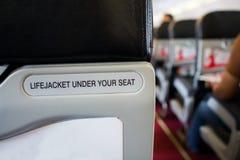 在您的位子标志下的救生衣,安全 免版税库存照片