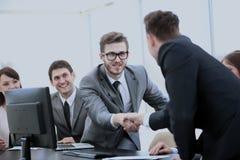在您的握手的书桌附近的商务伙伴作为咕咕声的标志 免版税库存照片