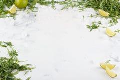 在您的文本下的白色背景 芝麻菜的石灰和绿叶在白色背景的 框架例证文本向量 免版税库存照片