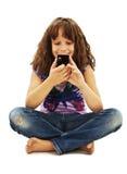 在您的移动电话的一点微笑的女孩读取sms 库存图片