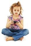 在您的移动电话的一点微笑的女孩读取sms 免版税库存图片