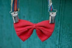 在悬挂装置的红色老蝶形领结在绿色背景 免版税库存图片
