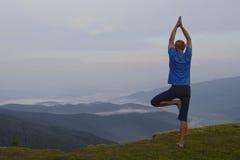 在悬崖的瑜伽 免版税库存图片