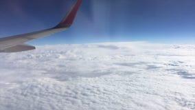 在惊人的云彩地平线和飞行飞机外面窗口的鸟瞰图飞过- 股票录像