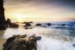 在惊人的日出背景的美好的海视图风景 击中海滩的阳光射线和软的波浪晃动 库存照片