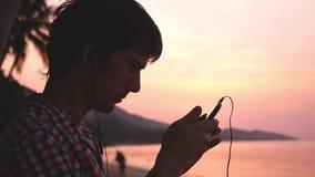在惊人的日落期间,年轻英俊的人举行手机听到在热带海滩的音乐 慢的行动 1920x1080 影视素材