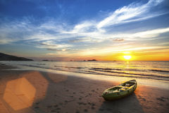 在惊人的日落期间,乘独木舟在海洋海滩 免版税库存照片