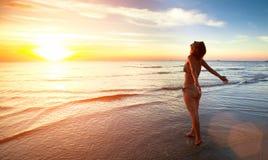 在惊人的日落期间,少妇站立往在海海滩的太阳 库存照片