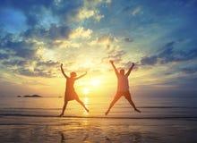 在惊人的日落期间,跳跃在海的年轻夫妇靠岸 免版税库存照片