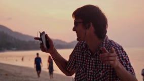 在惊奇期间,太阳镜的年轻英俊的愉快的人听到与手机和舞蹈的音乐在热带海滩 股票录像