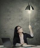 在想法电灯泡的女实业家开关 图库摄影