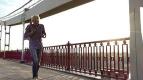 在愉快地跳跃与是姿态的桥梁和开始的年轻人电话在Slo Mo 股票录像