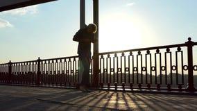 在愉快桥梁、跃迁高和奔跑的年轻人电话在日落在Slo Mo 影视素材