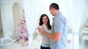 在愉快欢乐的心情的爱恋的夫妇花费结合在一起使手和跳舞在床旁边的时间在明亮的屋子里  股票视频