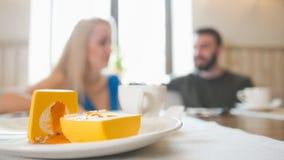 在愉快的夫妇前面的可口点心谈话在咖啡馆 免版税图库摄影