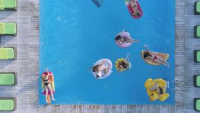 在愉快的女性朋友公司的寄生虫视图到在可膨胀的圆环和床垫的泳装游泳里在昂贵的水池 股票视频