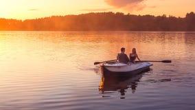 在愉快的妇女人r期间,浪漫金黄日落河湖雾爱恋的夫妇小划艇日期美丽的恋人一起乘坐 免版税库存照片