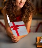 在愉快的妇女的特写镜头有圣诞节明信片的在厨房里 免版税库存图片