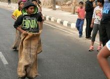 在愉快的路节目期间,人们演奏在路的套袋跑 免版税库存图片