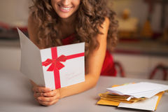 在愉快的年轻主妇读书圣诞节明信片的特写镜头 库存照片