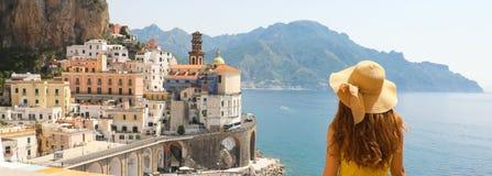 在意大利全景横幅的暑假 后面观点的有草帽和黄色礼服的少妇有阿特拉尼村庄的 免版税库存图片