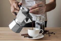 在意大利咖啡罐外面的倾吐的咖啡 库存照片