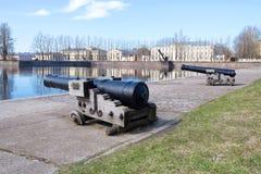 在意大利池塘的岸的两门老大炮5月下午 Kronstadt,俄罗斯 库存图片