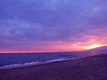 在意大利海滩的紫色日落 免版税库存图片