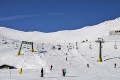 在意大利滑雪区域的驾空滑车在积雪的阿尔卑斯和滑雪者和挡雪板滑雪道的-冬季体育概念 免版税库存照片