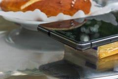 在意大利热奶咖啡旁边的手机 图库摄影