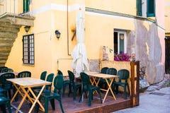 在意大利老村庄倒空与五颜六色的桌的露天咖啡馆在Cique Terre 图库摄影