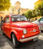 在意大利镇村庄意大利人标志的葡萄酒红色菲亚特500汽车 图库摄影