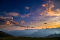 在意大利阿尔卑斯的庄严山峰、绿色牧场地和有雾的谷的五颜六色的阳光 在sunse的金黄cloudscape 免版税库存图片