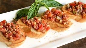 在意大利餐馆的Bruschetta开胃菜 蕃茄刷新foo 图库摄影