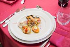 在意大利餐馆钓鱼快餐,在红色桌布的地中海烹调 库存照片