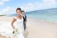在感到的海滩的新近地已婚夫妇画象愉快 免版税库存照片