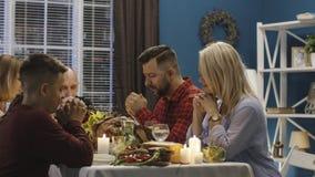 在感恩膳食前的家庭提供的祷告 免版税库存图片
