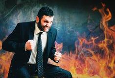 在愤怒灼烧的火的年轻商人 免版税库存照片
