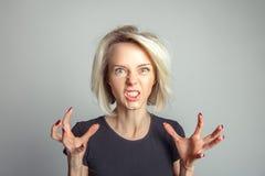 在愤怒的白肤金发的妇女咆哮声 免版税库存照片