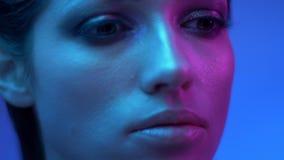 在慢慢地把变成和摆在照相机的五颜六色的紫色和蓝色霓虹灯的意想不到的时装模特儿在演播室 股票视频
