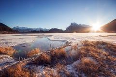 在慢慢地流动的河上的Beatutiful日出通过有闪耀草的,银朱的湖,班夫国家公园, Cana冻湖 图库摄影