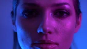 在慢慢地移动和观看入照相机的五颜六色的紫色和蓝色霓虹灯的明亮的时装模特儿在演播室 股票录像