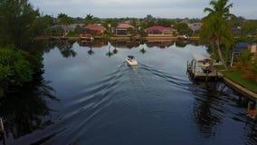 在慢慢地航行在热带风景的镇静深蓝色运河河水的小游船的惊人的天线4k视图 股票录像