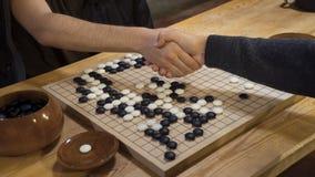 在戏剧中国棋前的手震动是或Weiqi 免版税库存图片