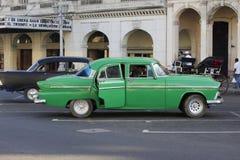 在戏院前面的绿色古巴汽车 免版税库存照片
