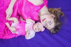 在我的母亲旁边的愉快的婴孩 免版税库存图片