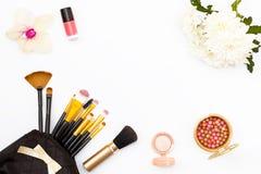 在我的钱包的构成刷子、指甲油、花、菊花和兰花和其他化妆用品在白色背景 最小的femi 库存照片