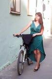 在我们的甚而在晚礼服骑自行车您能乘坐 在自行车旁边的模型 图库摄影