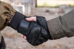在战争的战士握手 免版税库存照片